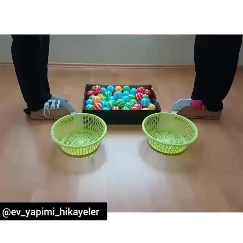 Переносим шарики в корзину с помощью картонной обуви.